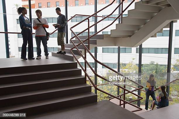 Students talking on staircase landing