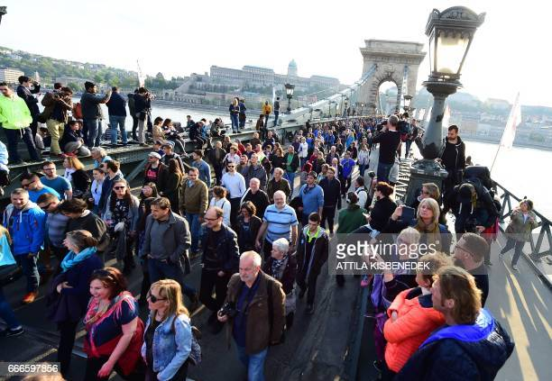 Students teachers of the Central European University and their sympathisers cross the oldest Hungarian bridge the 'Lanchid' during a protest march in...