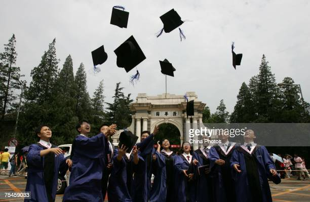 Students throw their mortar boards into the air as they graduate during a ceremony held at the Tsinghua University on July 18 2007 in Beijing China...