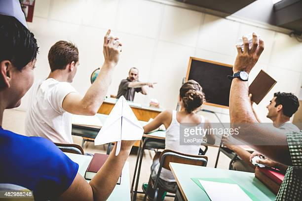 Students throwing papers to the teacher
