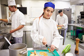 Students Training To Work In Catering Industry Chopping Vegetables. Looking To Camera