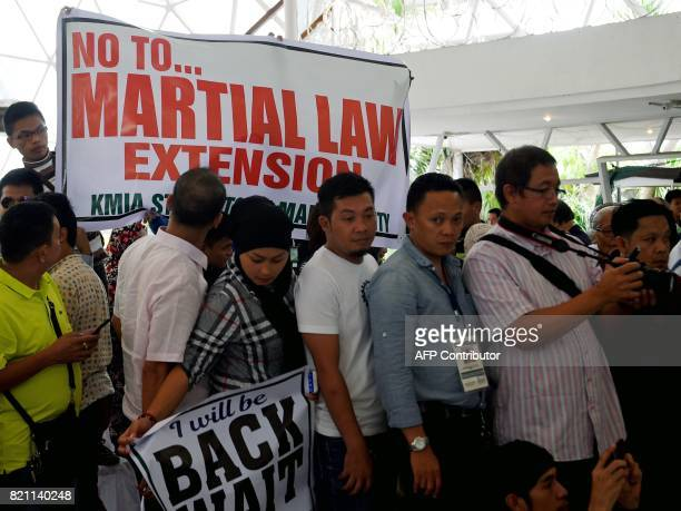 Students unfurl a protest streamer as Philippine Defense Secretary Delfin Lorenzana speaks during a dialogue with between displaced Marawi residents...