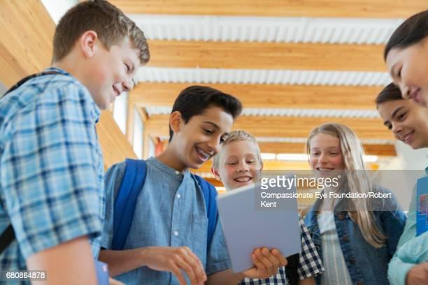 Students using digital tablet in corridor