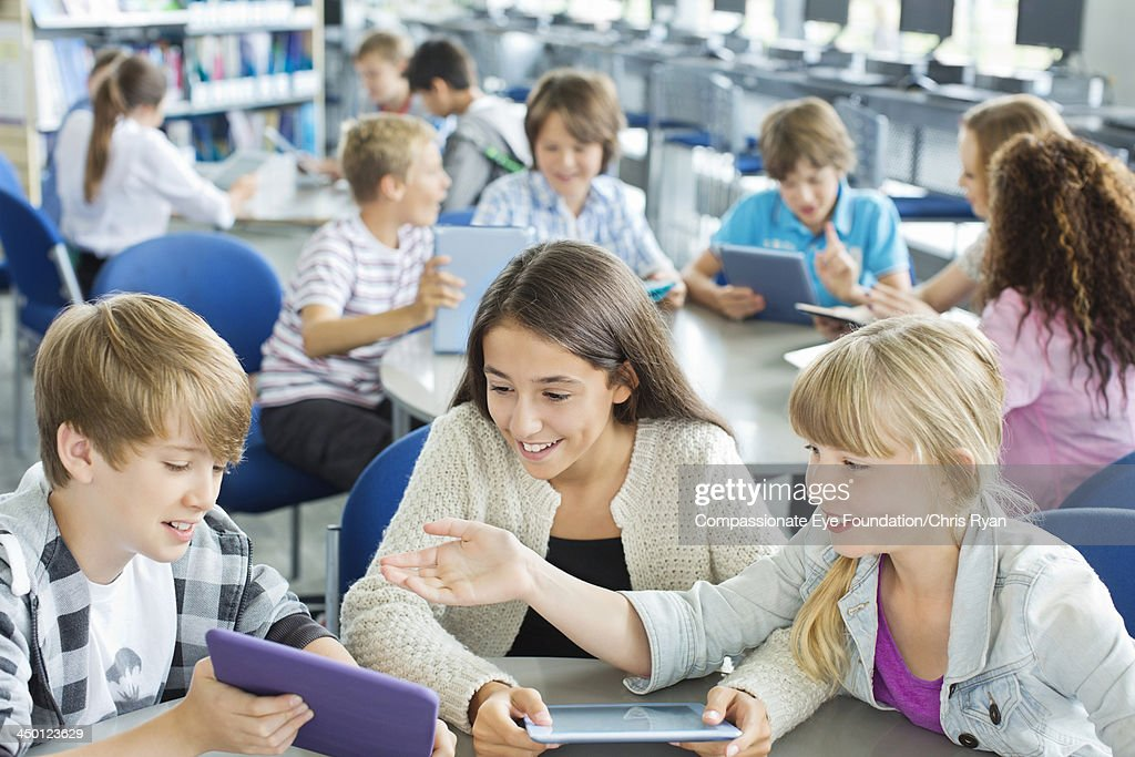 Students using digital tablets in classroom : Stock Photo