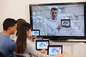 Students using digital tablets with instructor on monitor