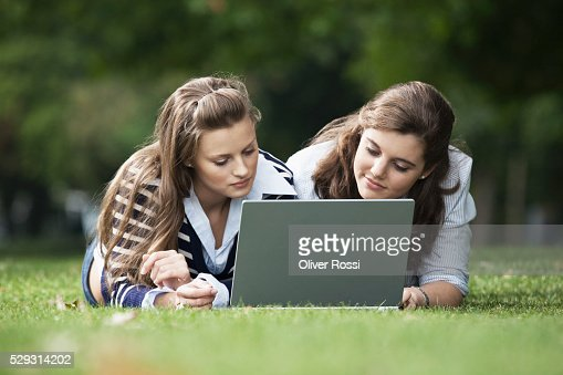 Students using laptop in grass : Stock-Foto
