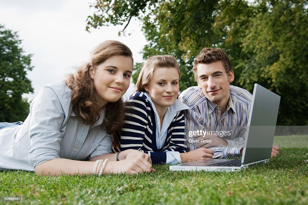 Students using laptop in grass : Foto de stock