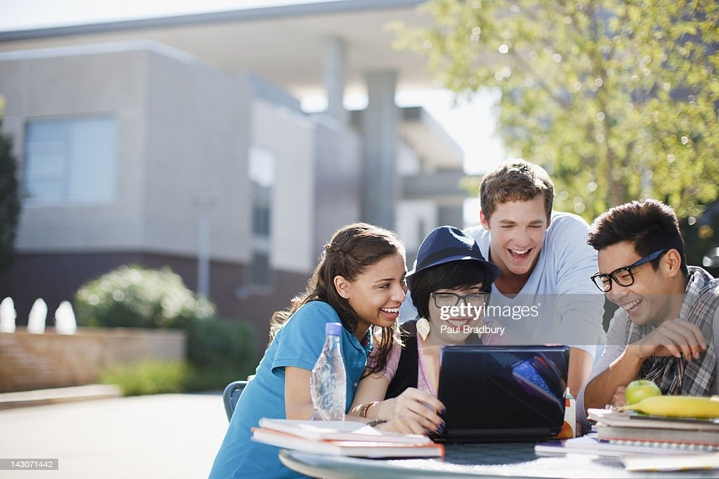 Students using laptop together outdoors : Stock Photo