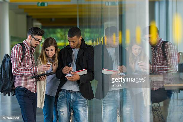 Students Using Mobile Phones In The Corridor