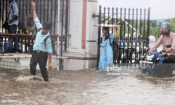 Students wade through waterlogged campus during heavy rains at Rajasthan University on August 23 2017 in Jaipur India