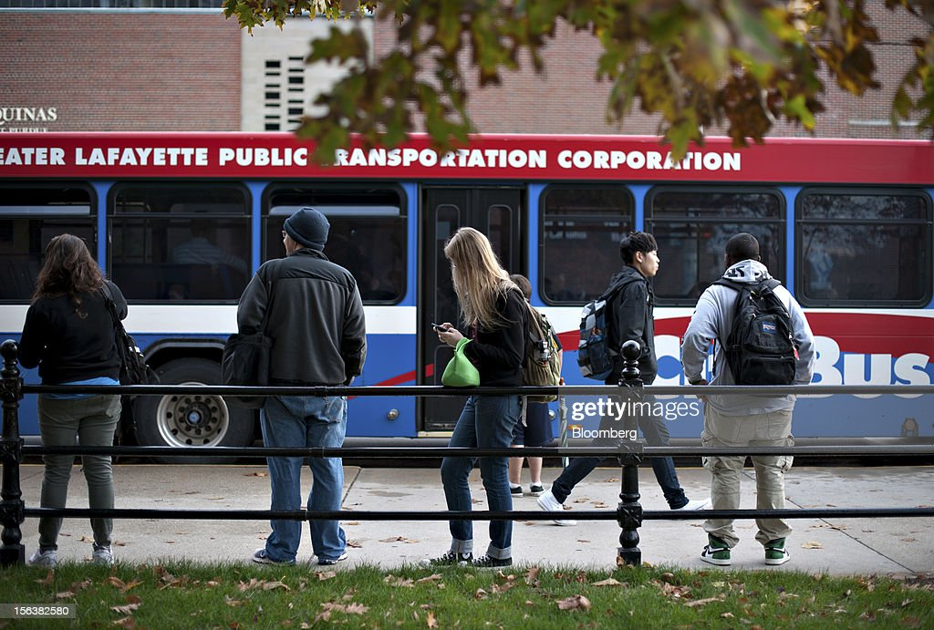 Students wait at a bus stop on the edge of the Purdue University campus in West Lafayette, Indiana, U.S., on Monday, Oct. 22, 2012. Administrative costs on college campuses are soaring, crowding out instruction at a time of skyrocketing tuition and $1 trillion in outstanding student loans. At Purdue and other U.S. college campuses, bureaucratic growth is pitting professors against administrators and sparking complaints that tight budgets could be spent more efficiently. Photographer: Daniel Acker/Bloomberg via Getty Images
