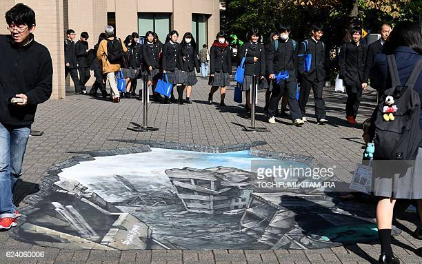 Students walk near a 3D optical illusion artwork of a devastated cityscape in Aleppo Syria at the campus of the Meiji University in Tokyo on November...