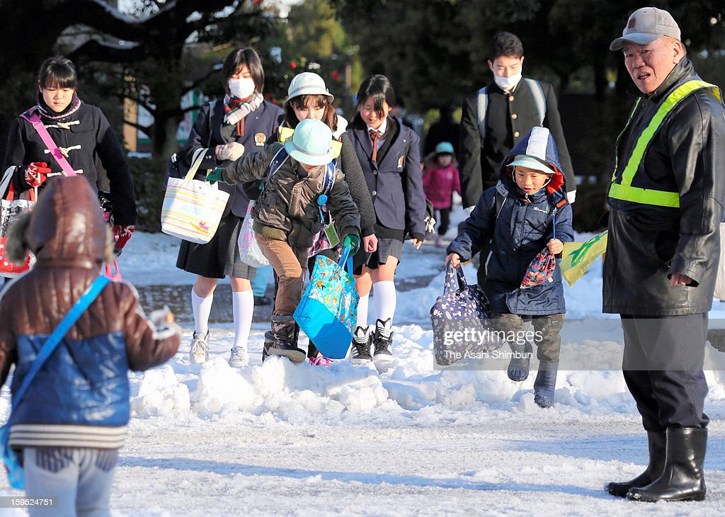 Students walk on a flozen road, a day after the snowfall on January 15, 2013 in Tokyo, Japan. A strong low pressure system caused heavy snow and strong wind in the coast area including Tokyo, more than 500 injured.