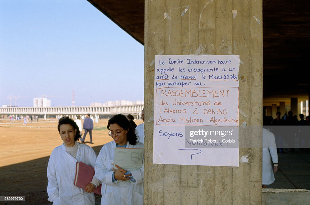 Students walk past a sign that asks teachers to stop work on November 22 in order to participate in a university-wide meeting at Bab-Ezzouar University in the suburbs of Algiers. Only a month before, in October 1988, hundreds of protesters, many of them students, were killed during anti-government riots.
