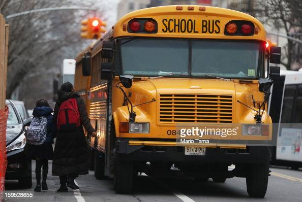 Students walk to board a school bus in Manhattan's East Village on January 15 2013 in New York City Drivers of the city's school buses are set to go...