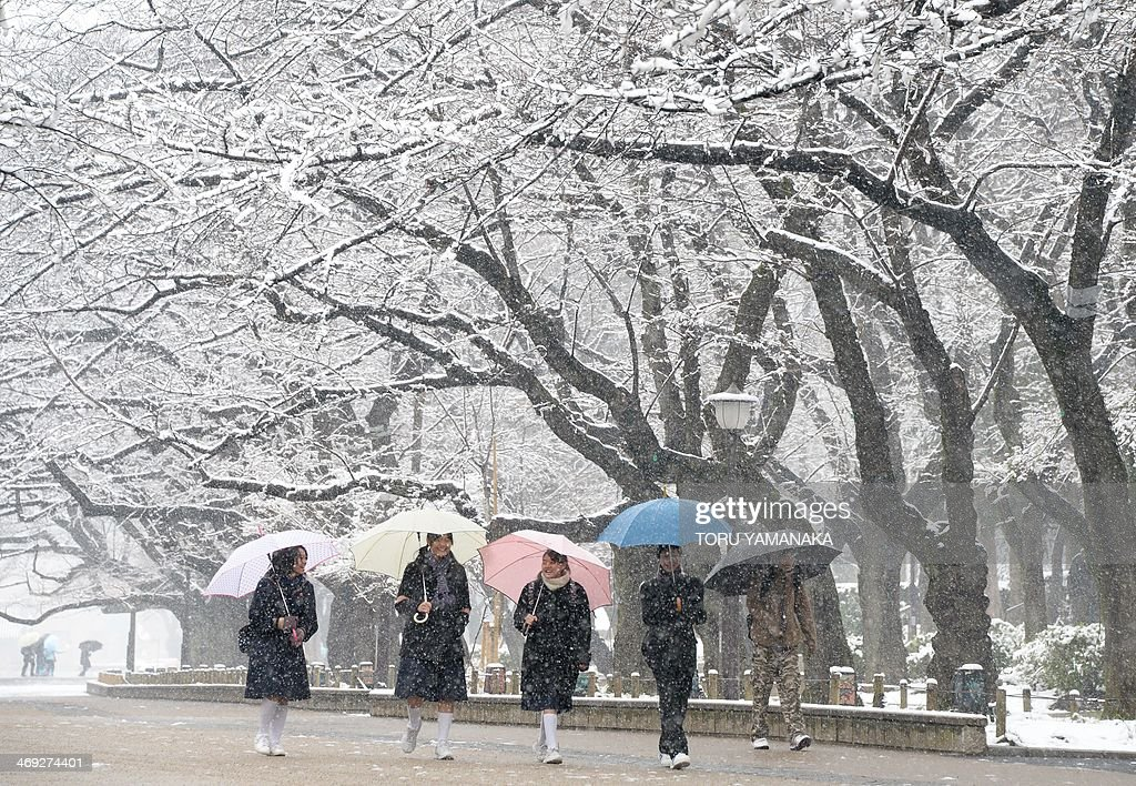 Students walk under snow covered trees at a park in Tokyo on February 14, 2014. Heavy winter weather is expected to hit Tokyo's metropolitan area again, bringing with it an estimated 10cm of snow. AFP PHOTO/Toru YAMANAKA