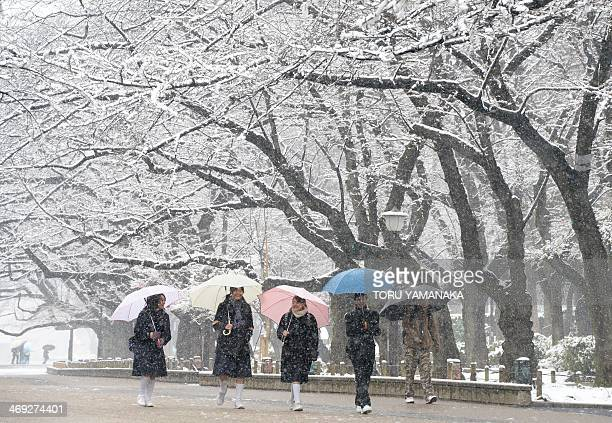 Students walk under snow covered trees at a park in Tokyo on February 14 2014 Heavy winter weather is expected to hit Tokyo's metropolitan area again...