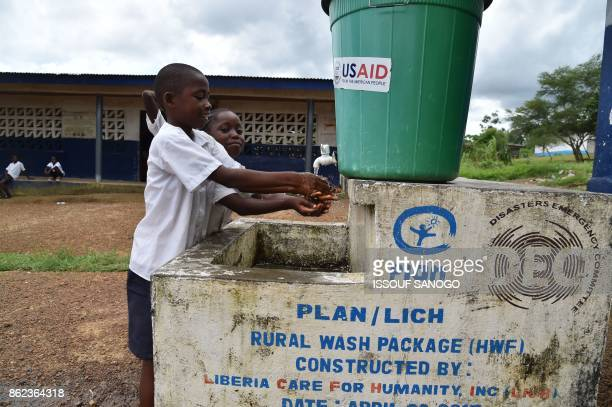 Students wash their hands outside the Cecelia Dunbar Public school in the city of Freeman Reserve in the Todee District about 30 miles north of...