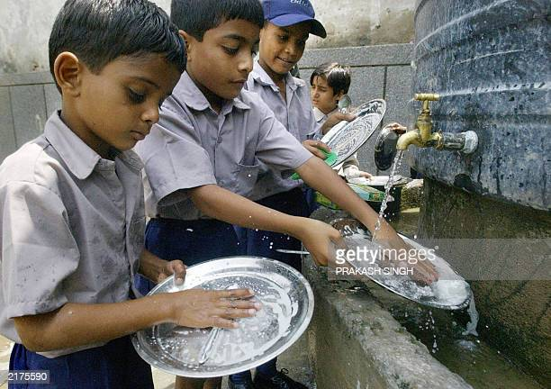Students wash their plates after having a midday meal distributed by International Society for Krishna Consciousness at a primary school run by...