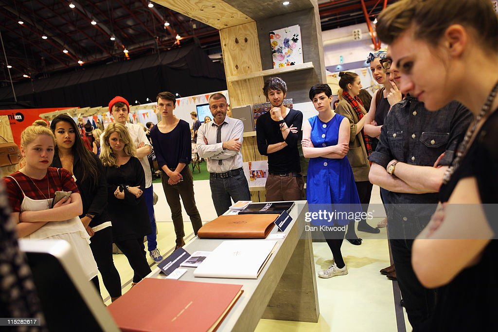 Students watch a monitor on an exhibition stand during Graduate Fashion Week at Earls Court on June 6, 2011 in London, England. The event which began in 1991 showcases emerging talent from BA Graduate fashion design courses across the UK and includes exhibition stands and catwalk shows from around 50 universities.