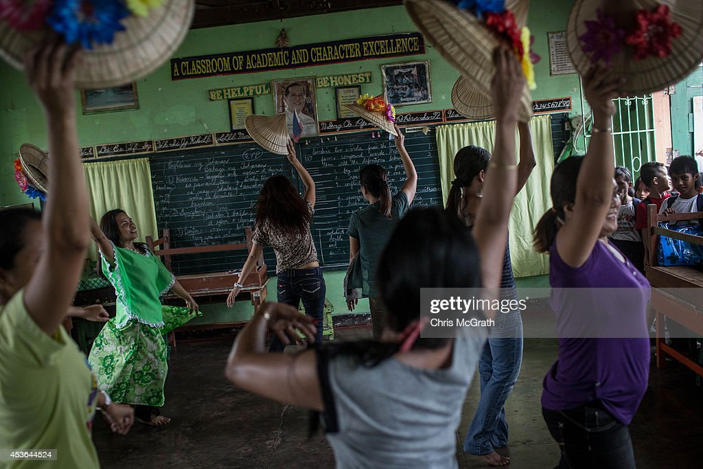 Students watch on as teachers from the San Fernando Central School practice a traditional dance for a school demonstration on August 15, 2014 in Tacloban, Leyte, Philippines. Residents of Tacloban city and the surrounding areas continue to focus on rebuilding their lives nine months after Typhoon Haiyan struck the coast on November 8, 2013, leaving more than 6000 dead and many more homeless. With many businesses and government operations back up and running and with the recent start of the years typhoon season, permanent housing continues to be the main focus with many families still living in temporary accommodation. As well as continuing recovery efforts Leyte is preparing for the arrival of Pope Francis, who will visit the region from January 15- 19.