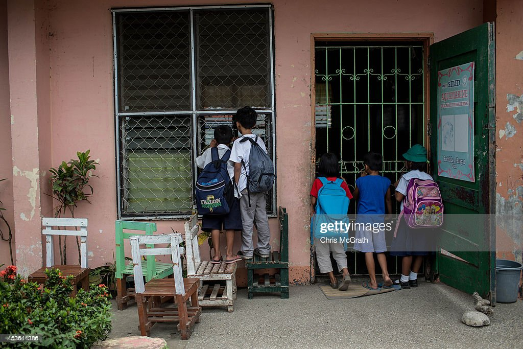 Students watch on through a classroom window as teachers from the San Fernando Central School practice a traditional dance for a school demonstration on August 15, 2014 in Tacloban, Leyte, Philippines. Residents of Tacloban city and the surrounding areas continue to focus on rebuilding their lives nine months after Typhoon Haiyan struck the coast on November 8, 2013, leaving more than 6000 dead and many more homeless. With many businesses and government operations back up and running and with the recent start of the years typhoon season, permanent housing continues to be the main focus with many families still living in temporary accommodation. As well as continuing recovery efforts Leyte is preparing for the arrival of Pope Francis, who will visit the region from January 15- 19.