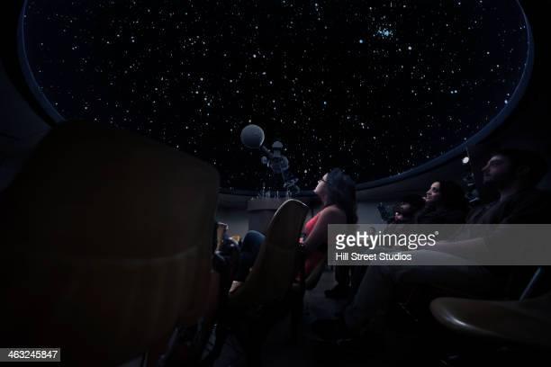 Students watching constellations in planetarium