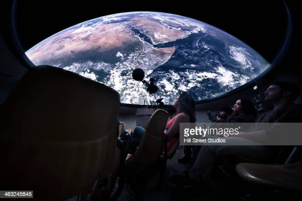 Students watching Earth in planetarium