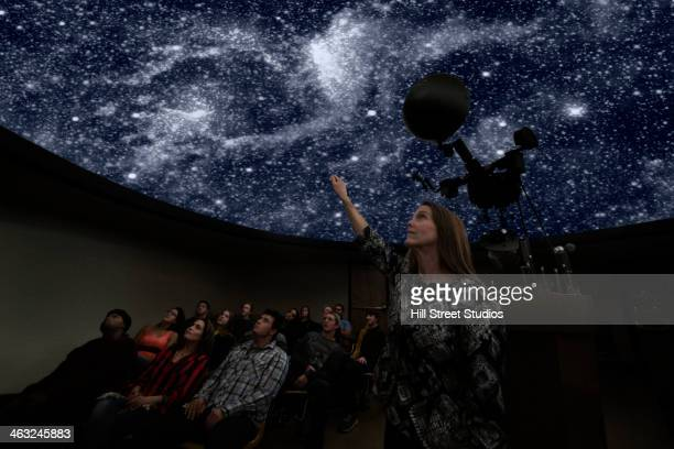 Students watching galaxy in planetarium