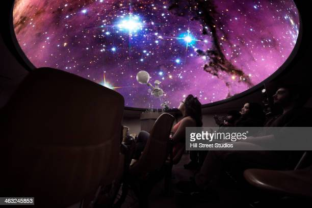 Students watching stars in planetarium