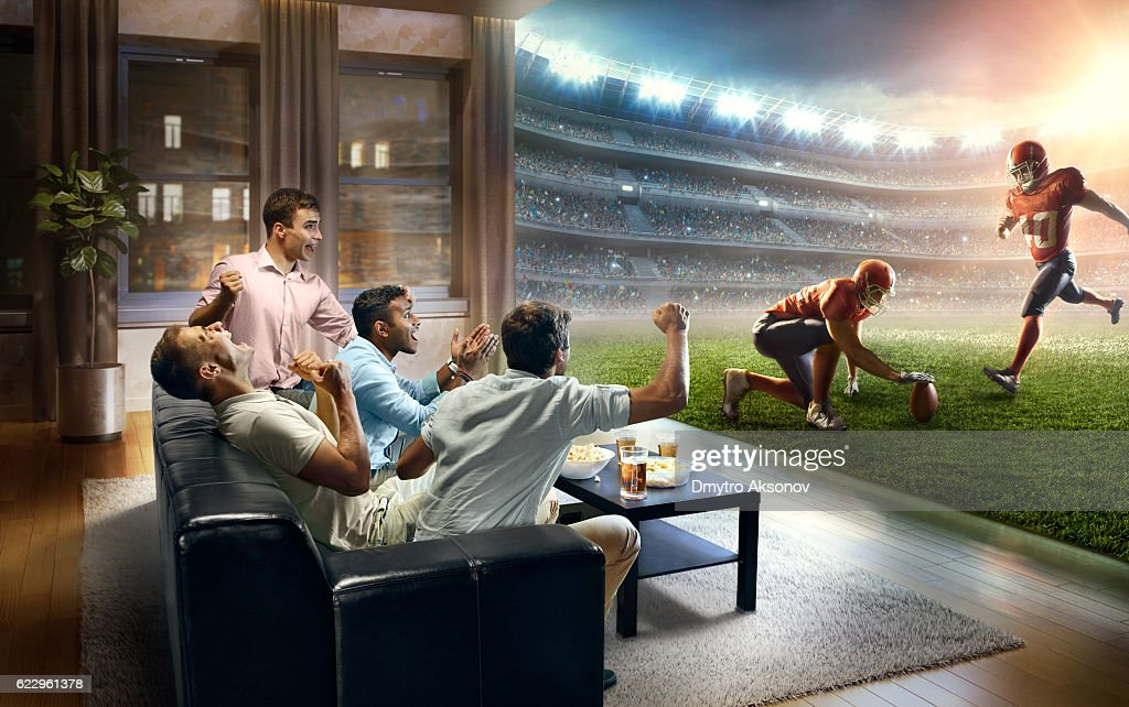 Students watching very realistic American football game at home : Stock Photo
