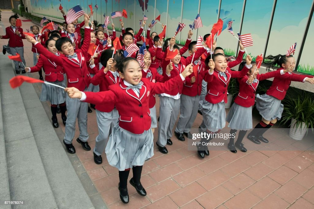 TOPSHOT - Students wave US and Chinese flags as they send off US First Lady Melania Trump and China's First Lady Peng Liyuan after their visit to the Banchang Primary School in Beijing on November 9, 2017. China's President Xi Jinping hosted US President Donald Trump at the imposing Great Hall of the People, next to Tiananmen Square, for the main event of the US president's five-nation tour of Asia. / AFP PHOTO / POOL / Ng Han Guan