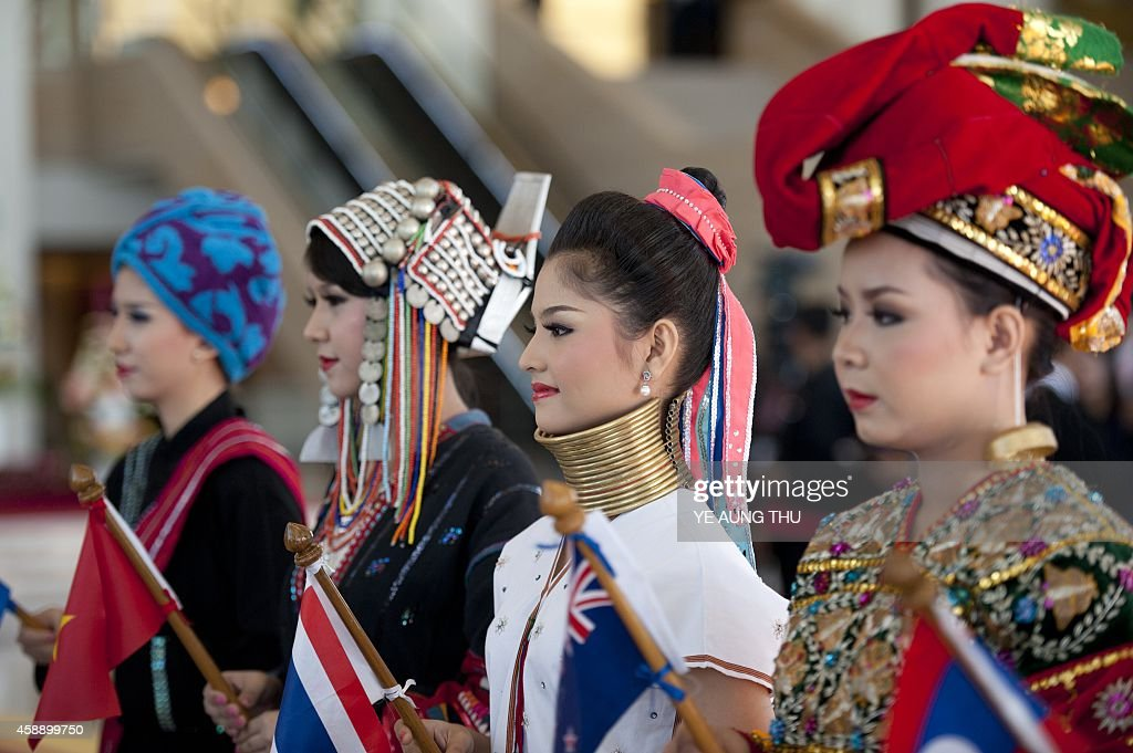 Students wearing costumes representing Myanmar's different ethnic groups welcome delegates as they arrive for the 25th ASEAN Summit at the Myanmar...