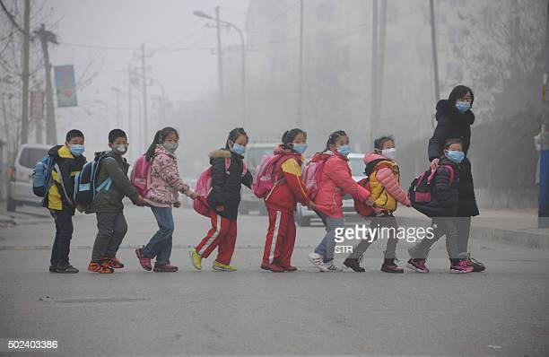 TOPSHOT Students wearing face masks walk across the street in a line in Jinan in east China's Shandong province amongst heavy air pollution on...