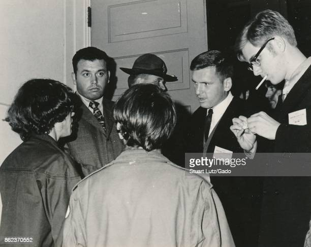 Students wearing hippie attire converse with welldressed men in suits smoking cigarettes in a tense scene during an anti Vietnam War student sitin...