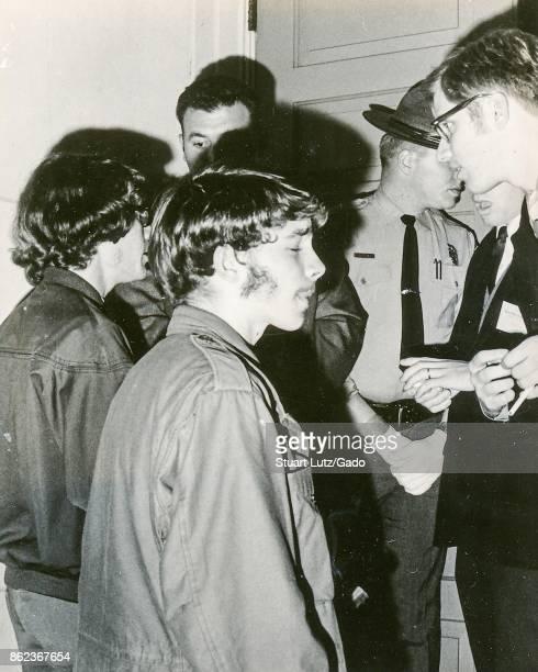 Students wearing hippie attire speak with sheriff's deputies in uniform during an anti Vietnam War student sitin protest at North Carolina State...