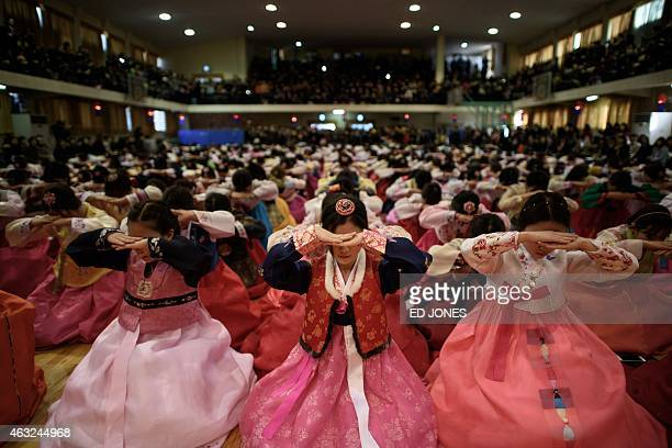 Students wearing traditional hanbok dresses bow as they attend a graduation and comingofage ceremony at the Dongmyeong girl's high school in Seoul on...