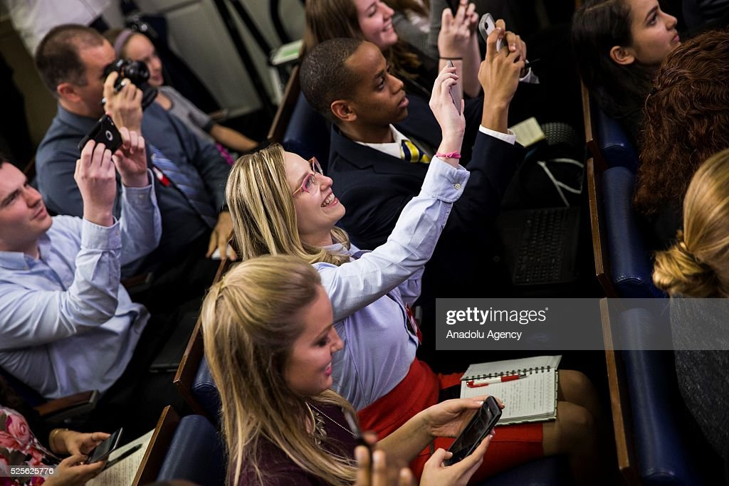 Students whip out their phones to snap photos of President Barack Obama makes an unexpected stop to answer questions from student journalists from colleges all over the United States in the Brady Press Briefing Room of the White House in Washington, USA on April 28, 2016.