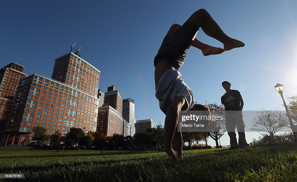 Students who do not live in the neighborhood practice gymnastics in a park in Lower Manhattan on October 22, 2012 in New York City. The Census Bureau reported last month that between 2000 and 2010 the downtown population grew by nearly 40,000 people, in spite of the September 11 terrorist attacks at the World Trade Center. One World Trade Center is scheduled to open in 2014 at the symbolic height of 1,776 feet and will be the tallest building in the Western Hemisphere.