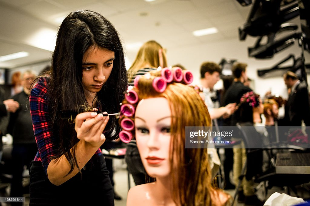 Students with an immigrant background working as a hairdresser with a dummy at the Vocational training center of the Chamber of Crafts (Bildungszentrum Butzweilerhof der Handwerkskammer) on November 24, 2015 in Cologne, Germany. German industry has complained in recent years of being unable to fill tens of thousands of trainee positions and some see the influx of nearly a million migrants this year as a possible opportunity to narrow the gap.
