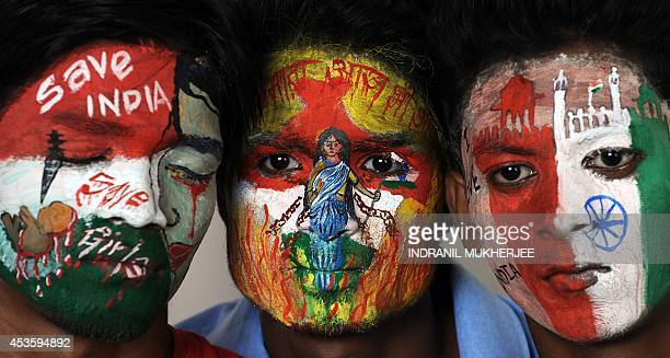 Students with social messages and the colours of the Indian tricolour painted on their faces pose on the eve of India's Independence Day in Mumbai on...