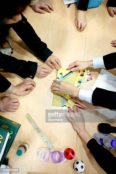 Students work together to solve a puzzle during a management training class at the McDonald's Corp Hamburger University in Shanghai China on Thursday...