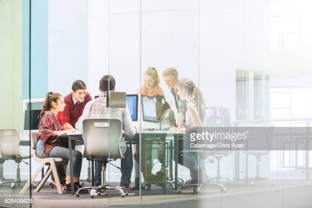 Students working with computers behind glass door