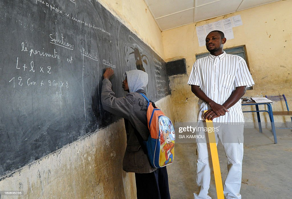 A students writes at the blackboard as the teacher looks on in a classroom in Gao, in the north of Mali, on the first day of the reopening of schools after the French bombing of Islamist targets, on February 4, 2013. Schools reopened today in Gao after the town was taken on January 26 by French and Malian forces from Islamists who had been occupying it for the last year.