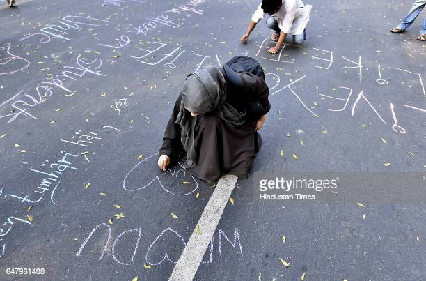 Students writing message on the Parliament Street road during the citizens protest march for Justice and Save Delhi University from Mandi house to...