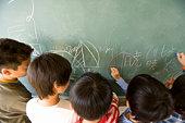 Students writing on blackboard