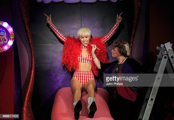 Studio artist Amy Harrington makes finishing touches to the new wax figure of Miley Cyrus at Madame Tussauds on March 17 2015 in London England