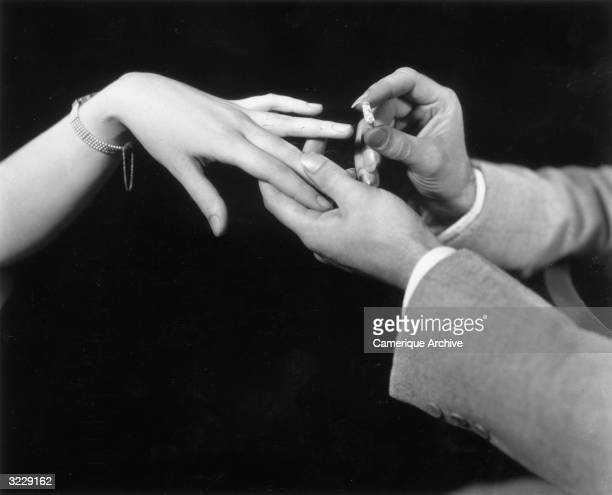 Studio closeup of a man's hand placing a diamond engagement ring on a woman's finger in front of a black background