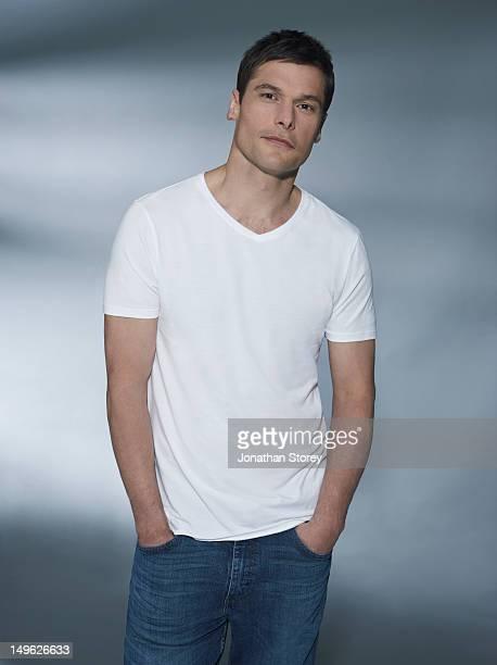 Studio front shot of male, hands in jean pockets