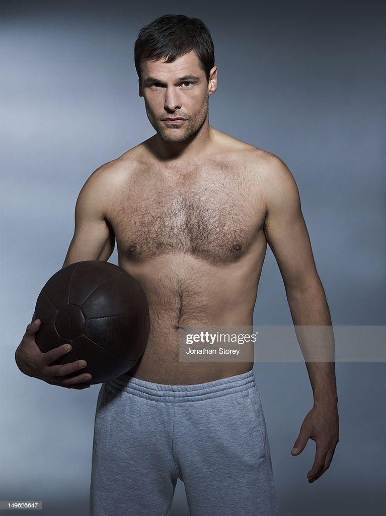 Studio front shot of male standing holding ball : Stock Photo